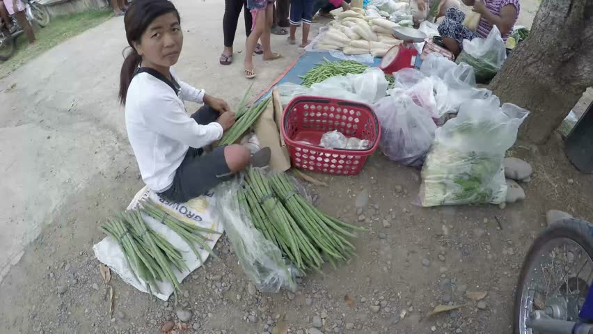 POTIA, IFUGAO, PHILIPPINES - APRIL 3, 2016: Woman braving street environment, to earn a meager living selling vegetables to sustain family.