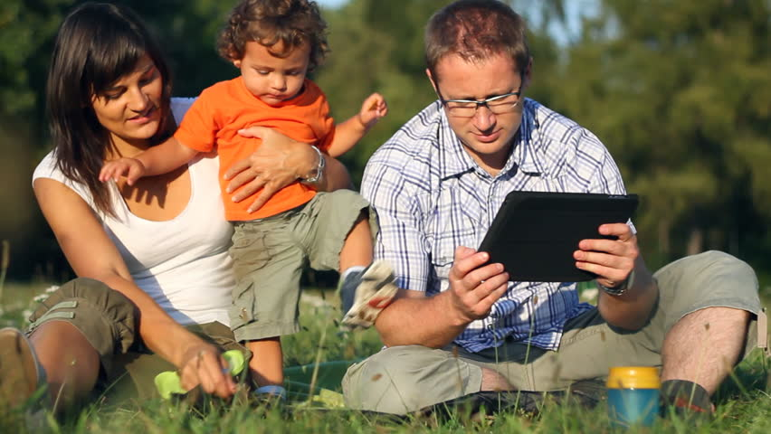 Happy family with tablet computer in the park, dolly shot  - HD stock footage clip