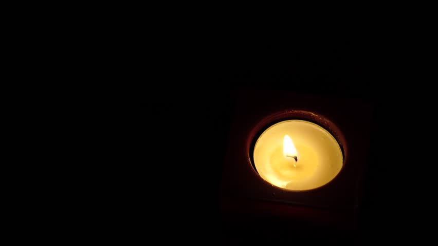Top down shot of round tea light candle burning in the dark. Lot of copy space. - 4K stock video clip