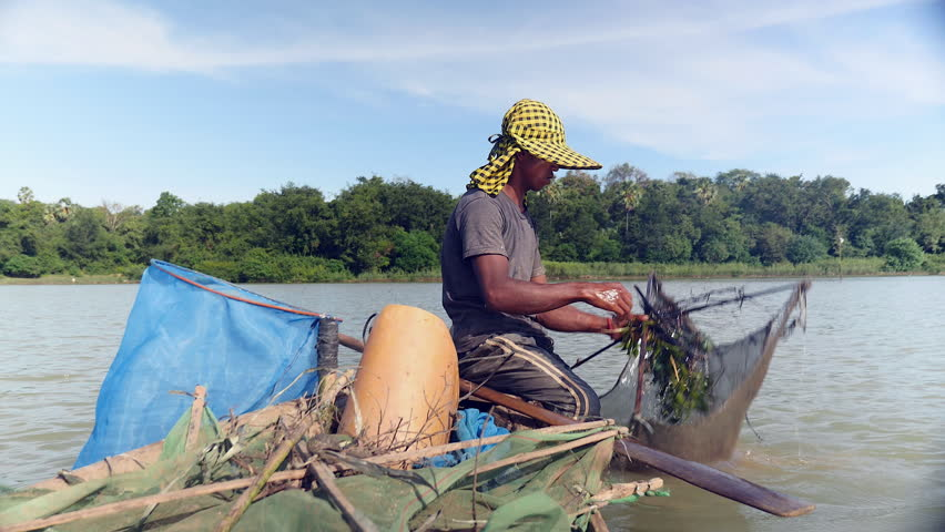 Close up of fisherman baiting net and dropping it deeper into river  with paddle for a new catch