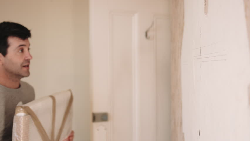 Adult couple fitting painting on the wall | Shutterstock HD Video #15757972