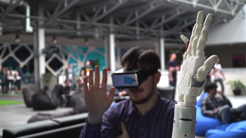 Ufa/Russia - 24 march 2016: Cybernetic robot arm, which controls people. Man controls robotic arm through virtual reality glasses. Playing game or the game lives in another world. Hand as the Skynet | Shutterstock HD Video #15787321