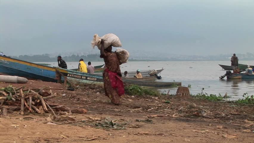 LAKE VICTORIA, UGANDA - CIRCA 2009: A heavily laden woman carries large parcels to a fishing boat circa 2009 on the shores of Lake Victoria. - HD stock video clip