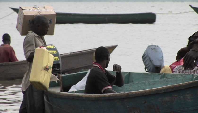 LAKE VICTORIA, UGANDA - CIRCA 2009: Fisherman loads boat circa 2005 along Lake Victoria. - HD stock footage clip