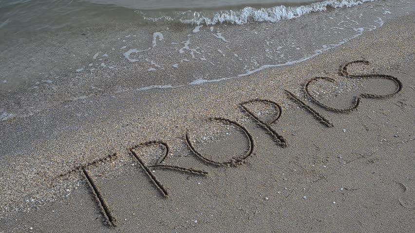 Inscription Tropics on sand on the beach. - HD stock footage clip