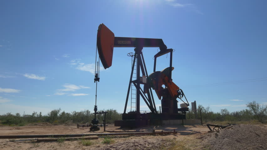 CLOSE UP: Industrial oil pump jack working and pumping crude oil for fossil fuel energy with drilling rig in oil field. Nodding donkey pump against the blue sky pumping over the sun in sunny summer - 4K stock video clip