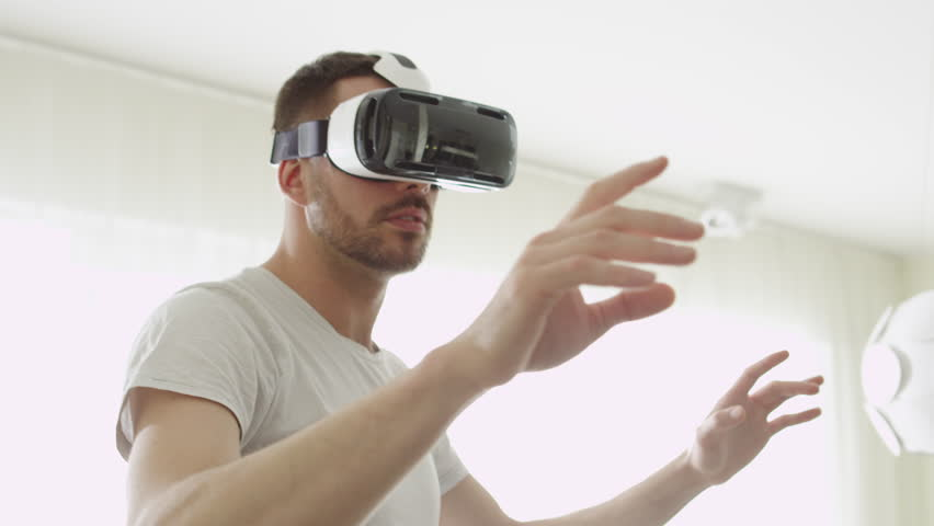 Man Wearing VR Headset at Living Room. Using Gestures with Hands. Shot on RED Cinema Camera. #15906697
