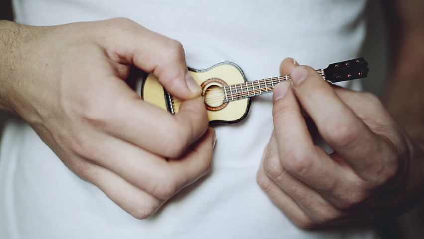 the person vigorously plays the small toy guitar close up