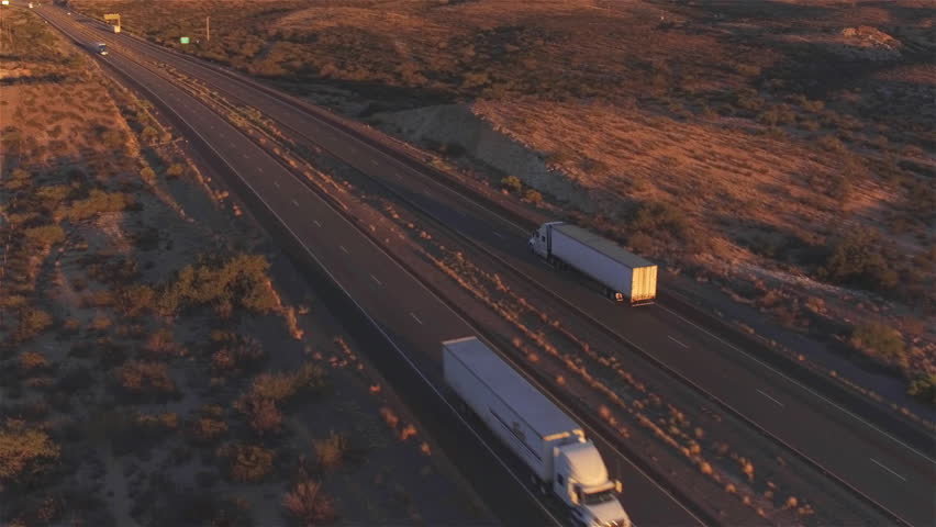4K AERIAL: Flying high above container semi truck transporting goods on busy highway across the country in beautiful summer evening. Traffic driving and speeding on busy freeway at golden sunset | Shutterstock HD Video #15953452