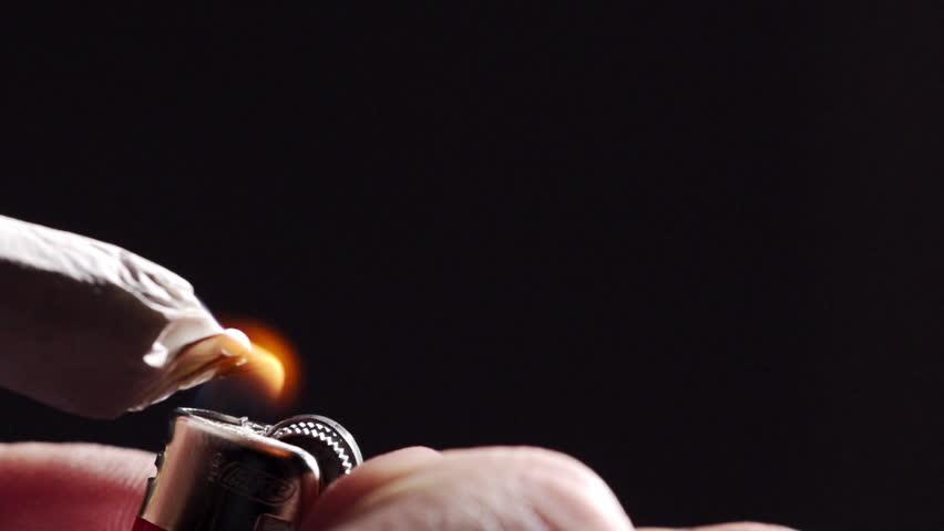 Close-up hand lighting a marijuana cigarette with a lighter
