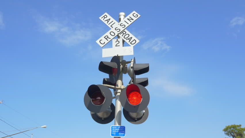 SLOW MOTION CLOSE UP: Level railroad crossing with barriers lowered and red lights flashing warning and announcing coming train on sunny day - 4K stock footage clip