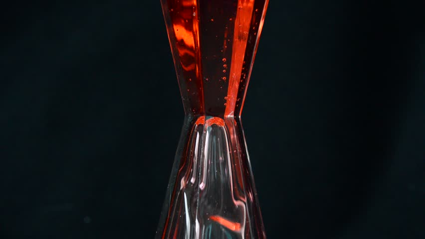 moving of red liquid in hourglass on black background - HD stock footage clip
