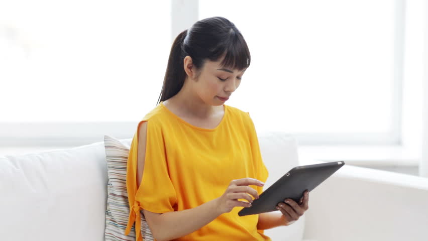 People, technology and leisure concept - happy young asian woman sitting on sofa with tablet pc computer at home   Shutterstock HD Video #16035226