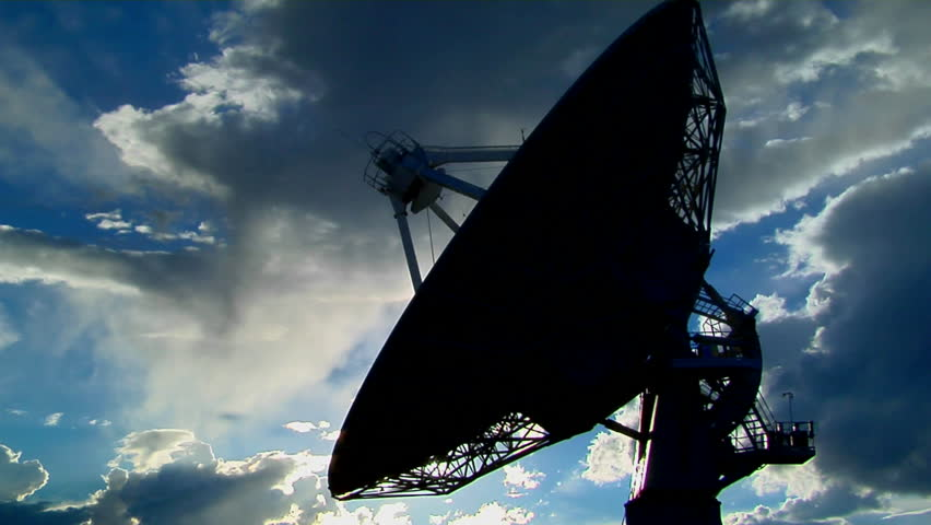 A satellite dish moves in time-lapse and is silhouetted against the sky - HD stock footage clip