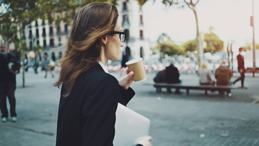 Close-up of young professional businesswoman walking outdoors, drinking coffee to go and holding modern portable computer or laptop, slow motion
