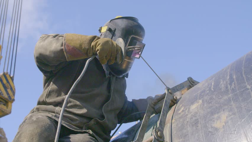 Industrial worker welding steel duct pipe by using metal torch in sunny winter day