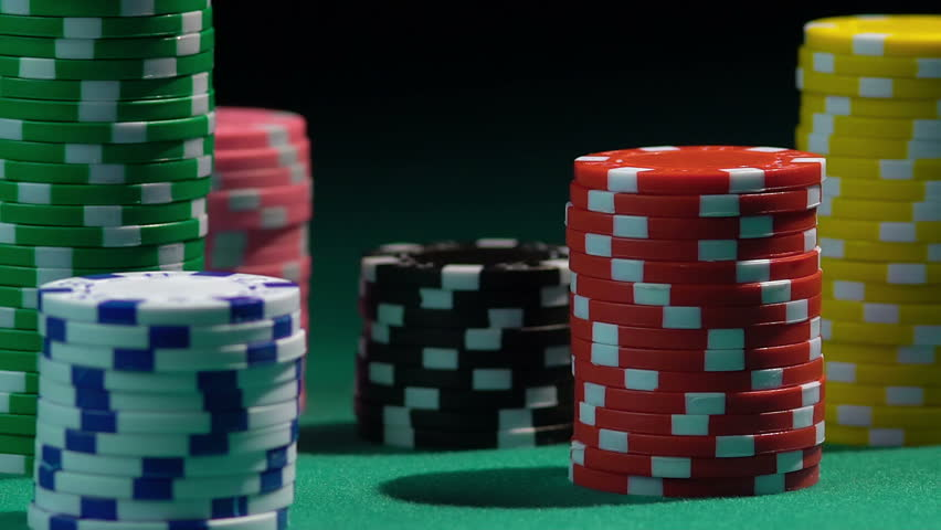 Stacks of colored poker chips on green casino table, red dice falling from above | Shutterstock HD Video #16103383