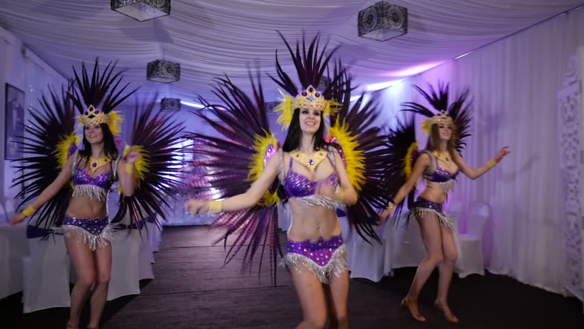 Three beautiful slim girl dancing samba in white decorated hall. Costumes in sequins and feathers. synchronously move.  - HD stock footage clip