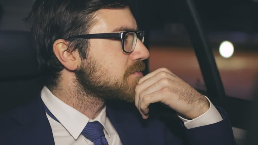Close up of tired businessman sitting in the back seat of taxi cab, looking in the window then taking off his eyeglasses and rubbing chin