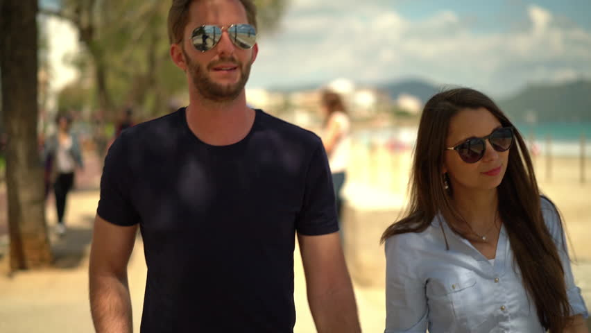 4k footage, young couple walking hand in hand on beach promenade on sunny day