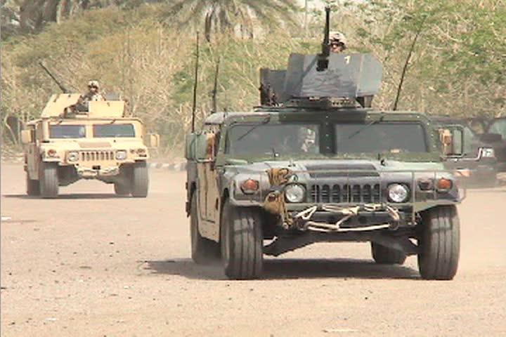 US Army armored Humvees head down a road in Iraq.