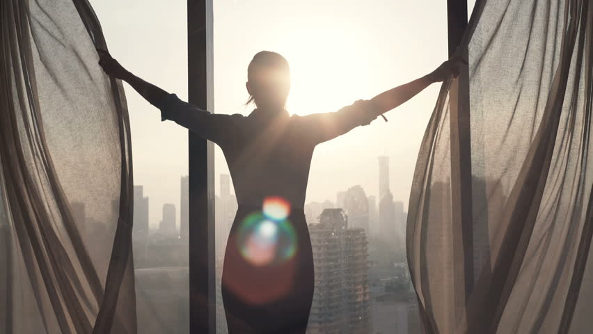 Young businesswoman unveil curtain and looking out of window