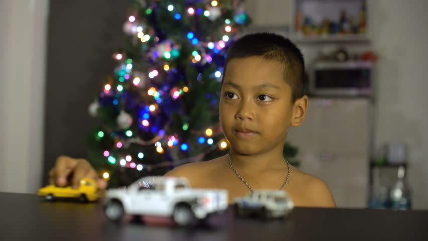 Little asian boy having fun with gift toy cars. Christmas lights on background 4k (3840x2160)