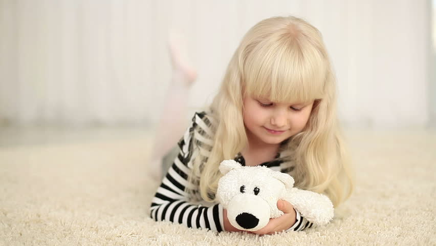 Happy girl with teddy bear looking at camera