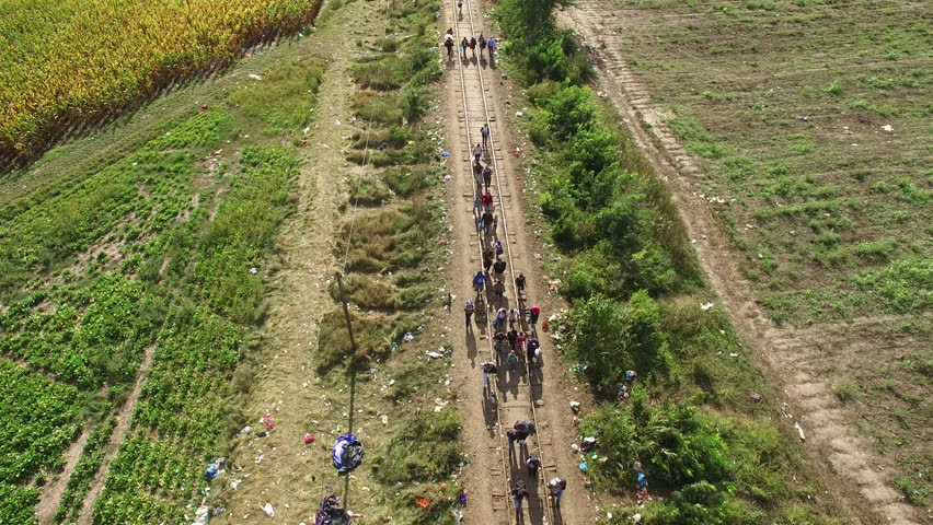 Aerial shot of refugees crossing at Hungarian - Serbian border, 14. September 2015. The day before Hungary closing the border. Peoples walking on rail. | Shutterstock HD Video #16501129