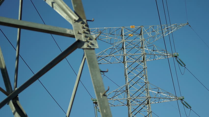 Pulling focus between two high tension electrical pylons used in part of the grid network infrastructure for the distribution and transport of electrical current by the utilities companies. - HD stock video clip