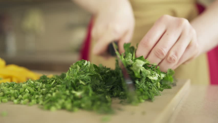Young woman preparing meal at the kitchen table. Good job for human health. Proper nutrition and wellness. Prepare and chop lush greenery for vegan. Eating at home. Food industry. Close up slow motion | Shutterstock HD Video #16524331