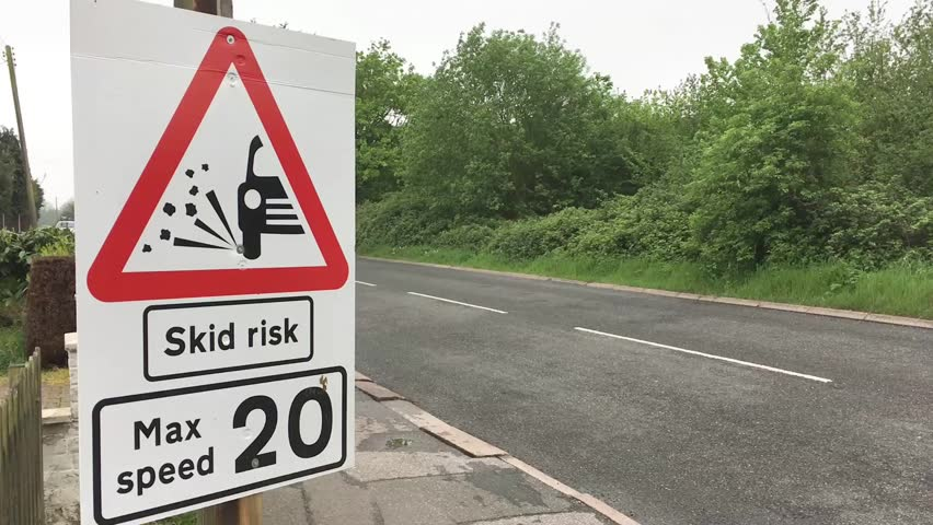 A skid risk warning sign on an english road  - HD stock video clip