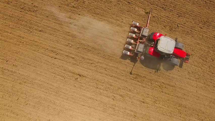 Camera flight over ploughed field with tractor. Industry and Agriculture in Czech Republic, European Union. - HD stock footage clip