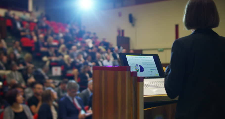 A woman holds a speech to the audience in an auditorium on a convention of economics and finance their business and to applaud his speech | Shutterstock HD Video #16575766