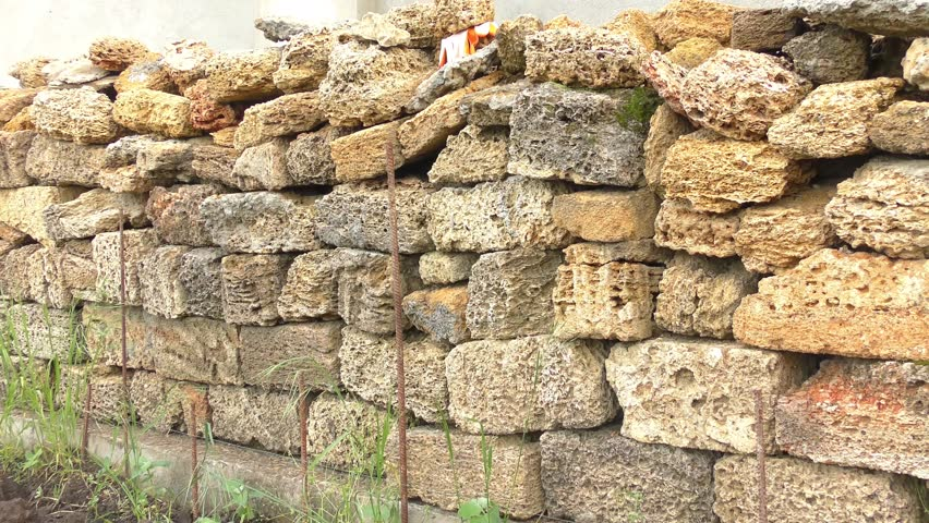 Yellow brick stack near wall - 4K stock video clip