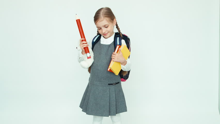 Cute schoolgirl 7-8 years with school knapsack holding books and big pencil and teddy bear and laughing at camera on white background