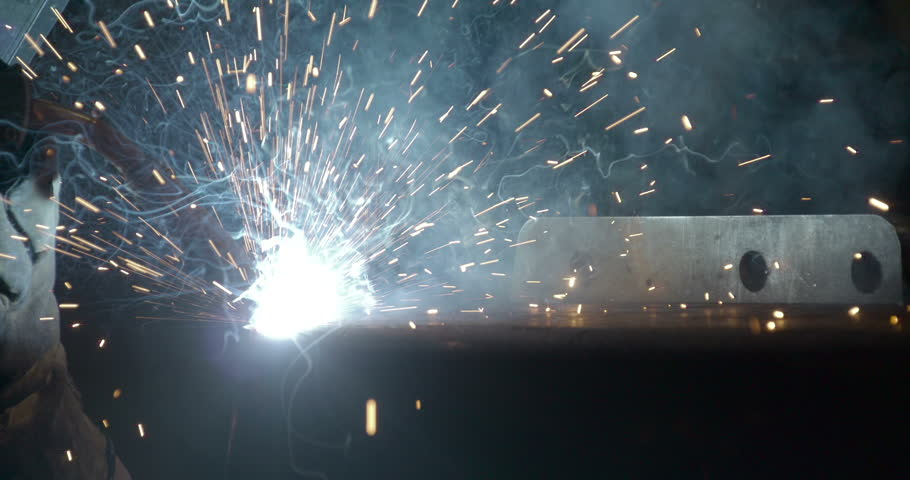 Attaching metal steel bars using the welding machine with the sparks of light coming from the machine - HD stock footage clip