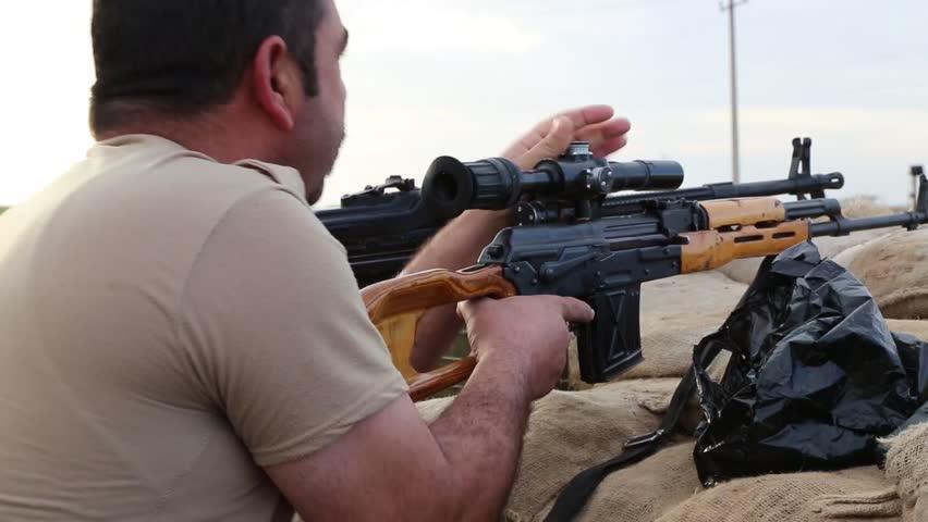 Iraq, February 2016: Pesh Merga sniper sitting with a spotter on Kurdish frontline near the border of Iraq, February 2016.Iraqi,