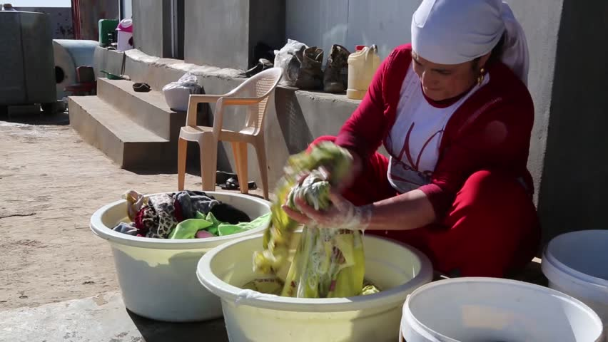 Iraq, February 2016: Iraqi woman cleaning bed clothes in a wash bucket in Iraq, February 2016: