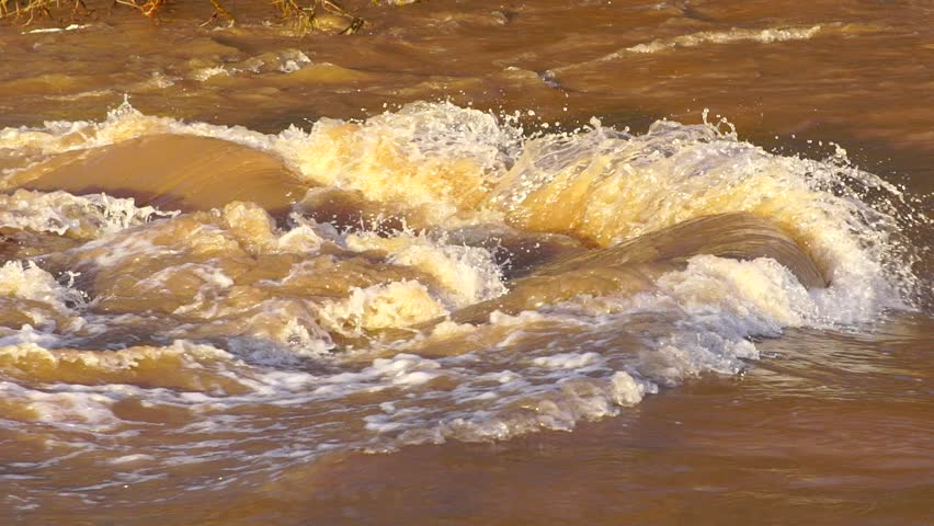 SLOW MOTION: Flash flood muddy river fast flowing. Flood river rushes, river raging. Natural disasters, stormy swollen river. Brown water flow. - HD stock video clip
