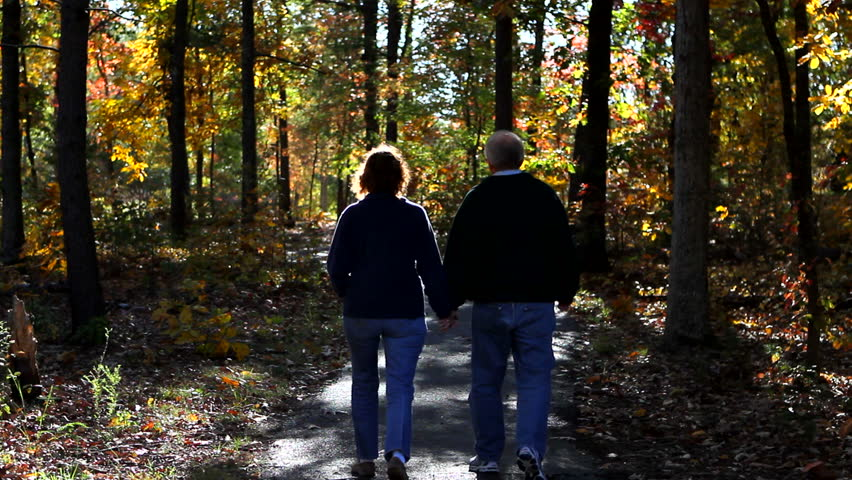 Mature loving couple walks down a pathway in the woods in autumn. They are bundled up for the cold. - HD stock video clip