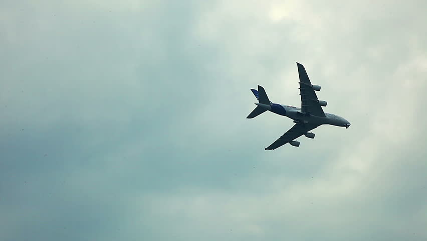 a380 air craft fly over horizon in cloudy sky - air show