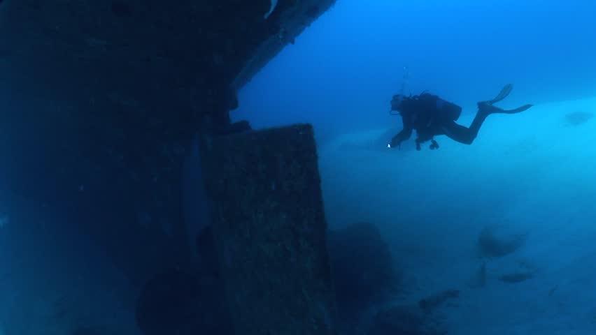 Divers exploring ship wrecks underwater