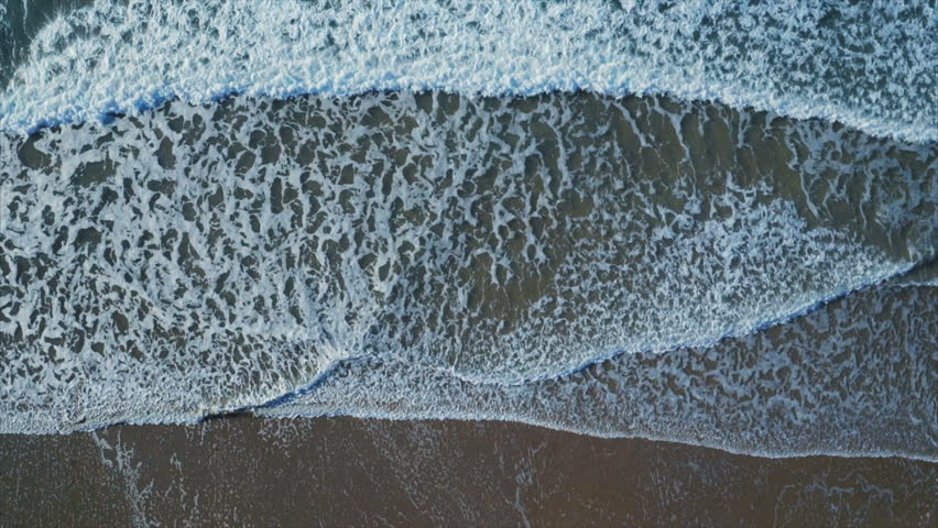 Aerial drone footage of sea waves crashing on shore. Slow motion of waves creating texture from the white sea foam. As the waves calm the appearance and patterns change. Overhead perspective. | Shutterstock HD Video #16825075
