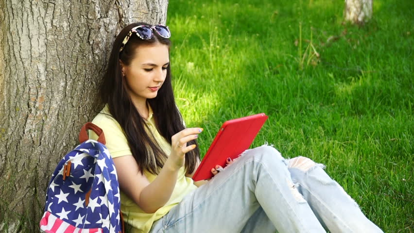 footage young beautiful woman sitting near a tree on the grass in the park and use the app in your comuter tablet. HD video