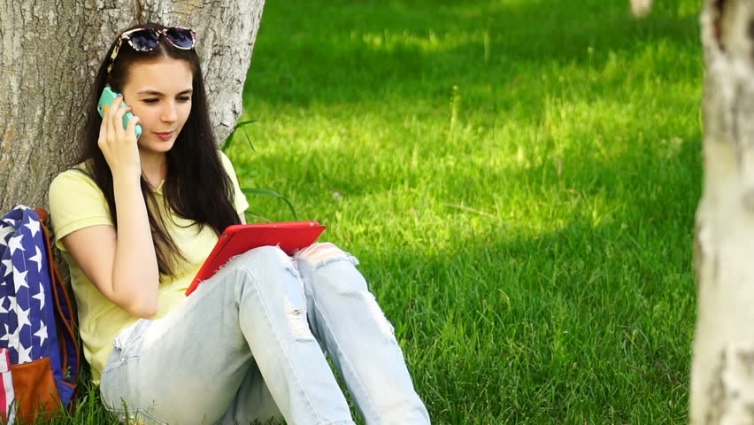 footage young beautiful woman sitting near a tree on the grass in the park, talking on smartphone and use the app in your comuter tablet. HD video