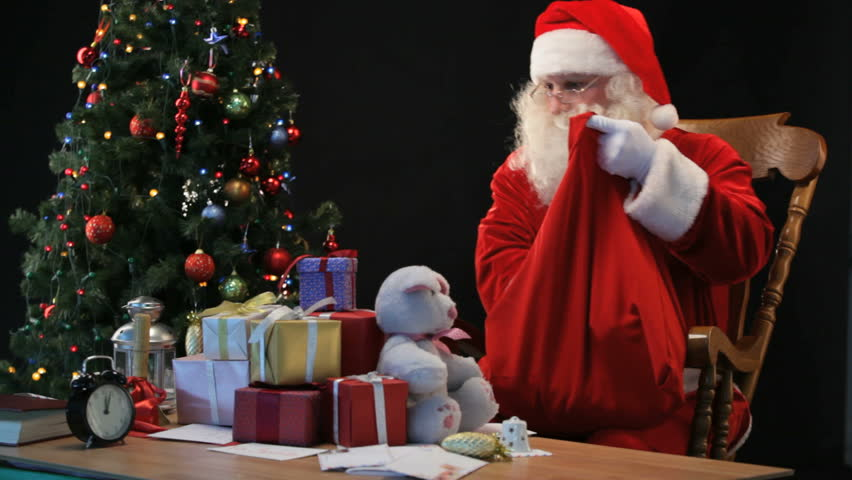 Santa Putting Wrapped Presents Into His Sack Stock Footage