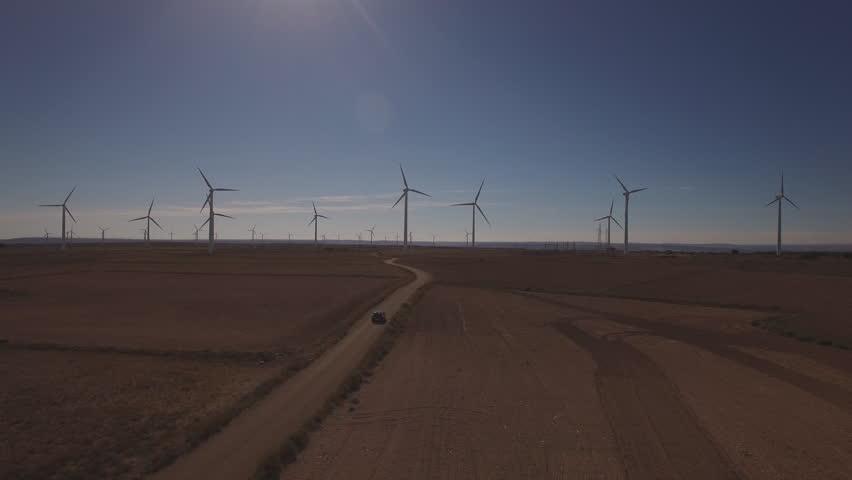 Aerial view of black car driving in windmill farm against sun, 4k