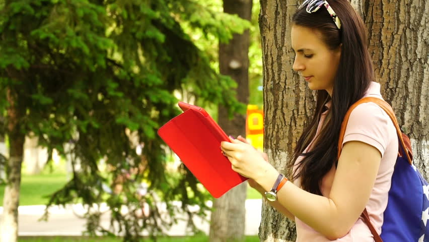 footage young beautiful woman standing near a tree on the grass in the park and use the app in your comuter tablet. HD video