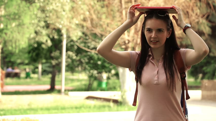 footage young beautiful woman walking in the park. girl put the tablet on his head. HD video